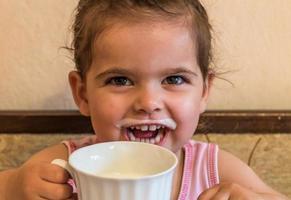 kleines Mädchen mit einem Glas Milch foto