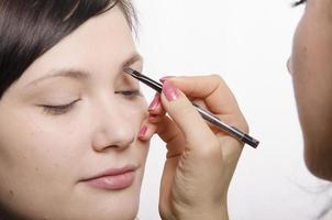 Maskenbildner bringt Augenbrauenstift Modell foto