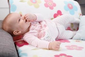 glückliches Baby, das auf Sofa liegt foto
