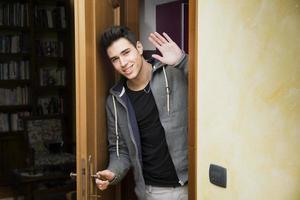 lächelnder junger Mann, der aus der Tür kommt und dem winkt foto
