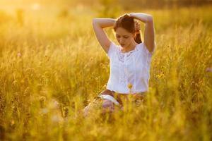 Frau sitzt auf dem Rasen und liest ein Buch foto