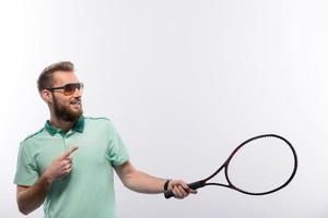 schöner junger Mann im Poloshirt, der Tennisschläger hält