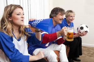 vielfältige Gruppe von Familienmitgliedern und Freunden, die sich ein Fußballspiel ansehen