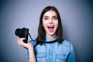 erstaunte junge hübsche Frau, die Kamera hält foto