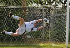Torhüter in der Luft, der einen Ball rettet