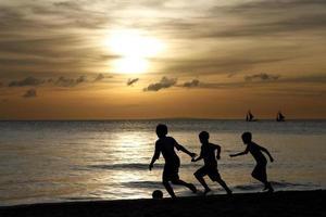 Silhouette der spielenden Kinder foto
