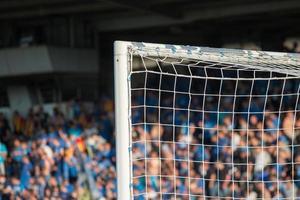 Torpfosten mit Fußballfans im Hintergrund