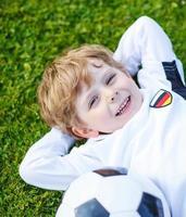 blonder Junge von 4 ruht mit Fußball auf Fußballfeld foto
