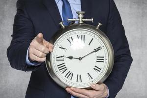 Geschäftsmann mit Uhr auf Sie zeigend