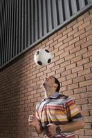 Mann, der Ball vom Kopf im Portikus abprallt foto