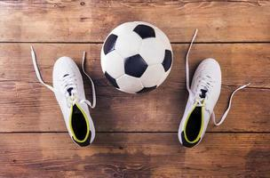 Fußballschuhe und Fußball auf Holzboden