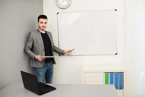 junger Geschäftsmann oder Lehrer, der Daten auf weißer Tafel zeigt