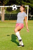 jugendlich Mädchen, das Fußball jongliert foto