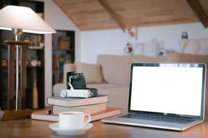 Stapel alter Bücher, offener Laptop und alte Kamera