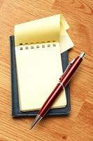 gelber leerer Notizblock mit Stift foto
