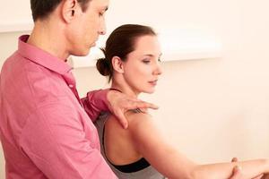 Orthopäde mit einem Patienten in Behandlung foto