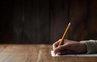 Frauenhand, die auf Papier schreibt foto