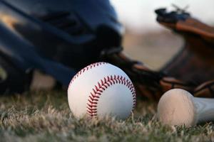 Holzschläger und Baseballhelm foto