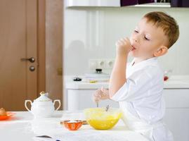 Schneiden Sie den kleinen Koch, der seine Teigmischung probiert foto