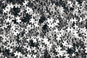 Stapel unfertiger Puzzleteile in monochromem Look foto