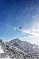 roter Hubschrauber im Flug in den Winteralpen mit Schneepulver