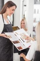 Die hübsche junge Friseurin bedient ihren Kunden foto