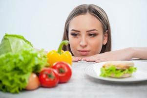 schöne junge Dame wählt zwischen gesundem und ungesundem Essen foto