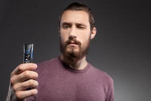 fröhlicher Mann mit Bart denkt über die Rasur nach