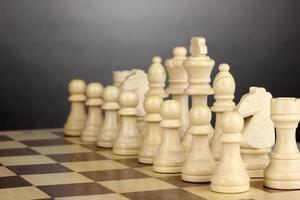 Schachbrett mit Schachfiguren auf grauem Hintergrund foto