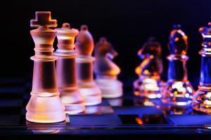 Glasschach auf Schachbrett beleuchtet von blauem und orangefarbenem Licht