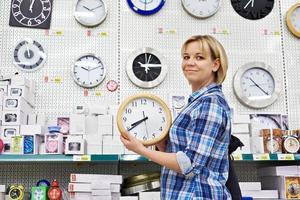 Frau wählt Wanduhr im Laden foto