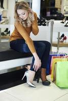 Frau kann sich nicht entscheiden, welche Schuhe sie kaufen soll foto