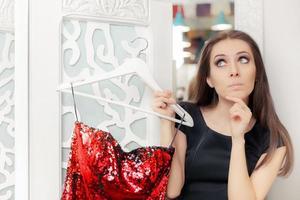 überraschtes Mädchen, das rotes Partykleid in der Umkleidekabine anprobiert foto