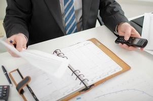 Geschäftsmann hält ein Dokument und ein Telefon foto
