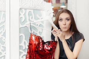 Erstauntes Mädchen, das rotes Partykleid in der Umkleidekabine anprobiert foto