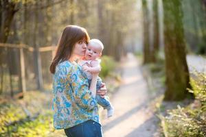 junge Mutter mit ihrem kleinen Baby im Wald foto