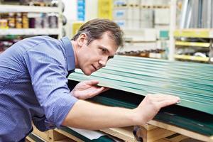 Mann wählt Metallprofil für Zaun im Laden foto