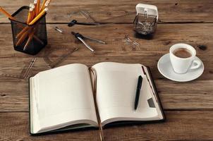 Öffnen Sie das Notizbuch auf einem Schreibtisch mit einer Tasse Kaffee foto