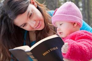 Mutter und kleine Tochter lesen Bibel foto