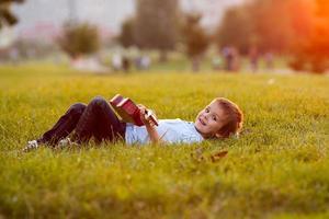 entzückender Junge mit Gitarre, sitzend auf dem Gras