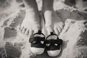 Kinderschuhe und Mamas Füße.