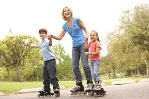Großmutter und Enkelkinder laufen im Park Schlittschuh