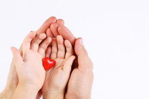 Männer- und Babyhände halten zwei rote Herzen foto