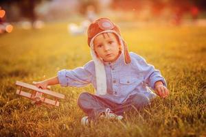 süßer Junge, der mit Flugzeug auf Sonnenuntergang im Park spielt