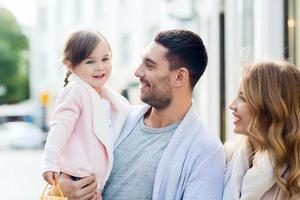 glückliche Familie mit Kind und Einkaufstaschen in der Stadt foto