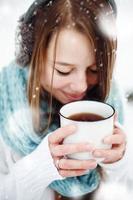 Frau trinkt heißes Getränk im Freien im Winter