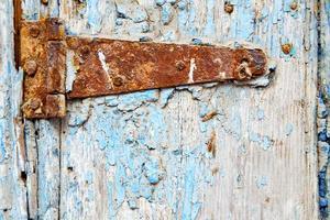 Marokko im alten Holzfassadenhaus und im rostigen sicheren Vorhängeschloss foto