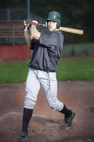 Baseballspieler schwingender Schläger foto