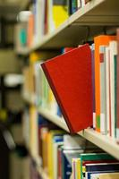 rotes Buch, das aus einem Bücherregal herausspringt