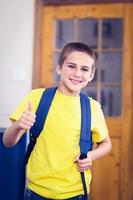 lächelnder Schüler mit Schultasche, die Daumen hoch in einem Klassenzimmer tut foto